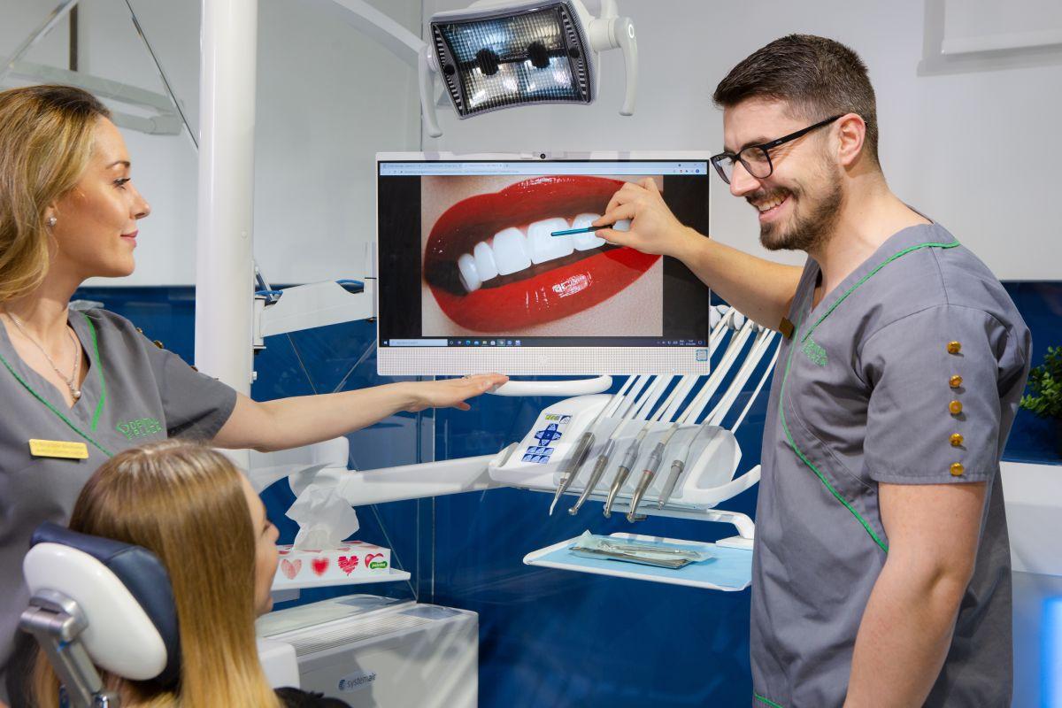 stomatolog pokazuje na snimak zuba